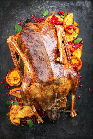 Traditional roasted stuffed Christmas duck with orange and pomegranate as top view on a board