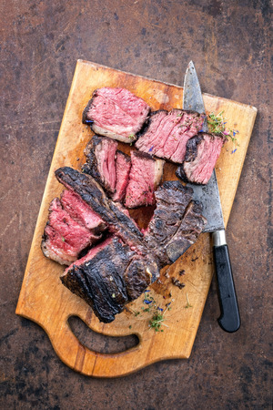 Traditional barbecue dry aged wagyu porterhouse steak sliced as top view on a rustic cutting board with herbs