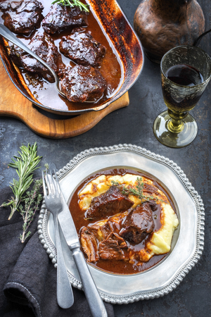 Traditional German braised veal cheeks in brown sauce with mashed potatoes as top view on a pewter plate
