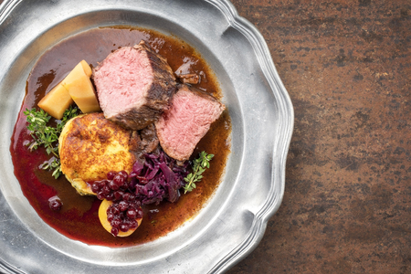 Traditional saddle of venison with fried mashed potatoes and red cabbage in game red wine sauce as top view on a pewter plate with copy space right