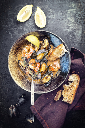 Traditional French Corsican seafood stew with prawns and mussels as top view in a modern design Japanese bowl