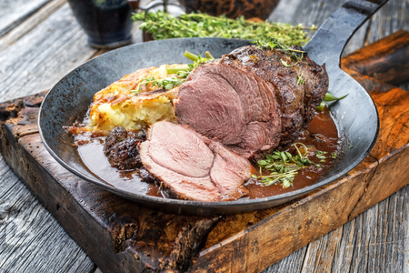 Barbecue roast boar joint with roesti and game red wine sauce as top view in a wrought-iron pan Stock Photo