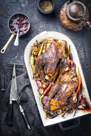 Traditional barbecue pheasant with vegetable and cranberry sauce as top view in a stewpot Stock Photo