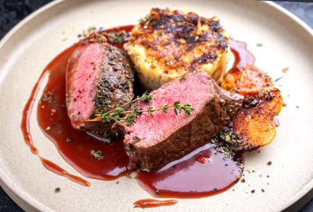 Traditional saddle of venison with Swiss rösti, quince and orange slices in game red wine sauce as closeup on a modern design plate Stock Photo