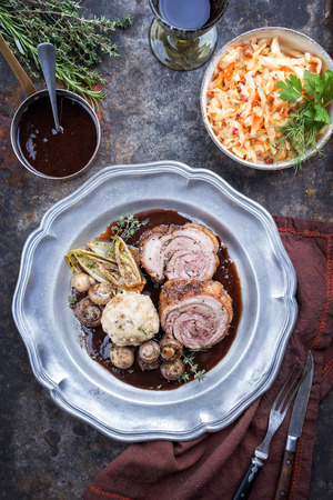 Traditional rolled boar roast with bread dumpling, fried chicory and mushroom as top view on a pewter plate with game red wine sauce Stockfoto