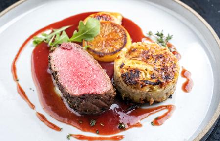 Selle traditionnelle de chevreuil avec rösti suisse, tranches de coing et d'orange dans une sauce au vin rouge en gros plan sur une assiette au design moderne Banque d'images