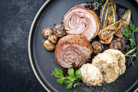 Traditional rolled boar roast with dumpling, fried vegetable and mushroom as top view on a modern design plate with game red wine sauce with copy space left