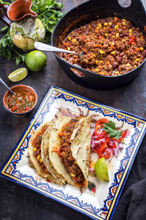Traditional slow cooked Mexican chili con cane with tortillas as closeup on a colored plate Stok Fotoğraf