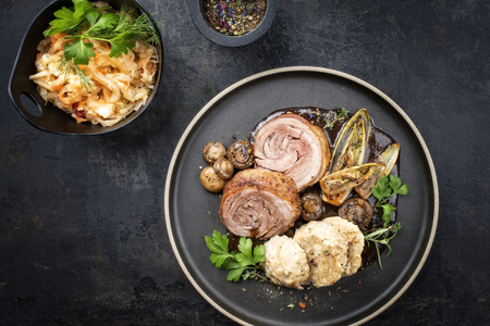 Traditional rolled boar roast with dumpling, fried vegetable and mushroom as top view on a modern design plate with game red wine sauce Stockfoto