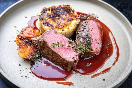 Traditional saddle of venison with Swiss rösti, quince and orange slices in game red wine sauce as closeup on a modern design plate Stockfoto