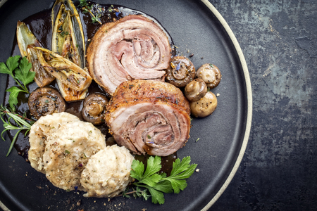 Traditional rolled boar roast with dumpling, fried vegetable and mushroom as top view on a modern design plate with game red wine sauce with copy space right Stockfoto
