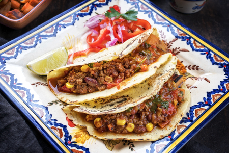 Traditional slow cooked Mexican chili con cane with tortillas as top view on a colored plate