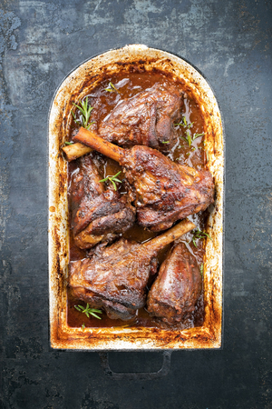Traditional barbecue leg of lamb in tomato red wine sauce and herbs as top view in a stewpot with copy space