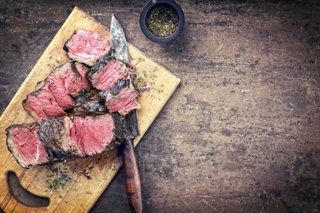 Traditional barbecue dry aged wagyu porterhouse steak sliced as top view on a rustic cutting board with copy space right Banco de Imagens