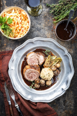 Traditional rolled boar roast with bread dumpling, fried chicory and mushroom as top view on a pewter plate with game red wine sauce Stock Photo