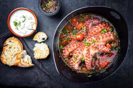 Pulpo tradicional griego braseado con tomates y hierbas en salsa ouzo con tzatziki como vista superior en una cacerola de hierro fundido