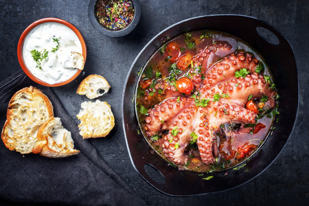 Traditional Greek octopus braised cooked with tomatoes and herbs in ouzo sauce with tzatziki as top view in a cast-iron saucepan Stockfoto
