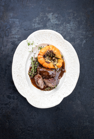 Traditional German braised pork cheeks in brown red wine sauce with mushroom and pumpkin as top view on a shabby chic design white plate with copy space