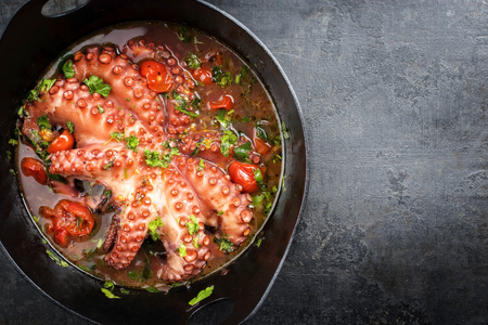 Traditional Greek octopus braised cooked with tomatoes and herbs in ouzo sauce as top view in a cast-iron saucepan with copy space right