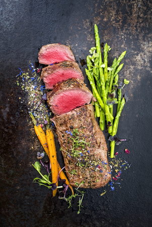 Traditional barbecue aged venison backstrap roast with green asparagus, carrots and herbs as top view on a rustic metal sheet Stock Photo