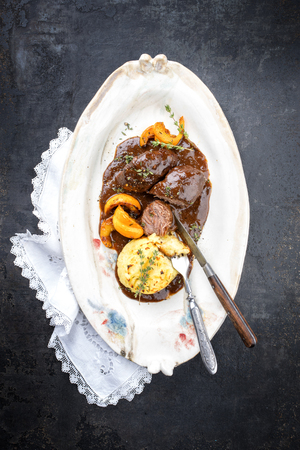 Traditional German braised pork cheeks in brown red wine sauce with fried mushed potatoes and pumpkin as top view on a shabby chic design white plate with copy space Stock Photo