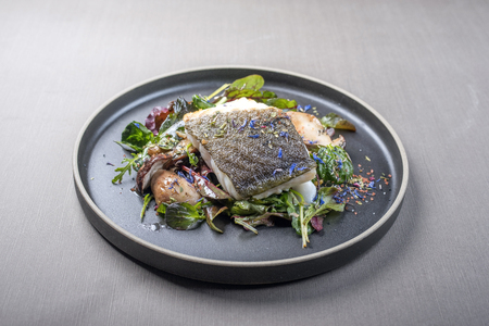 Fried Danish skrei cod fish filet with porcini mushroom and lettuce as closeup on a modern design plate with copy space