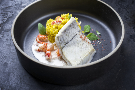 Fried haddock filet with saffron rice and shell prawns in crab sauce as closeup on a modern design bowl