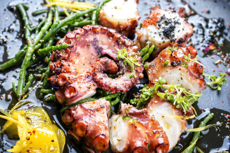 Traditional French octopus braised cooked with Salicornia, lemon curd and spice as macro closeup on a modern design plate Stock Photo