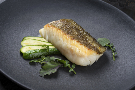 Fried Danish skrei cod fish filet with baby zucchini and lettuce as closeup on a modern design plate