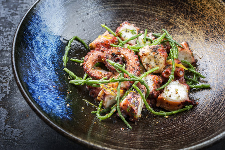 Traditional French octopus braised cooked with Salicornia, lemon curd and spice as closeup in a modern design Japanese bowl