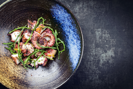 Traditional French octopus braised cooked with Salicornia, lemon curd and spice as top view in a modern design Japanese bowl with copy space right Stock Photo