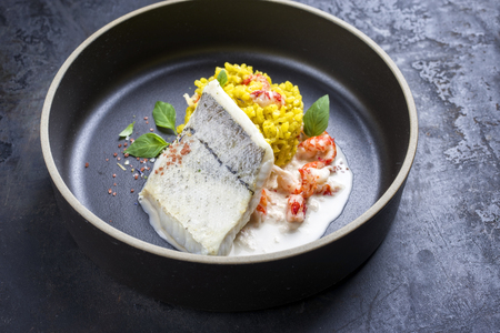 Fried haddock filet with saffron rice and shell prawns in crab sauce as closeup on a modern design bowl with copy space Stock Photo