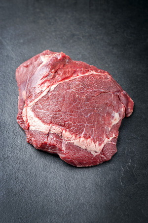 Traditional German raw beef cheeks as closeup on a black board Stock Photo