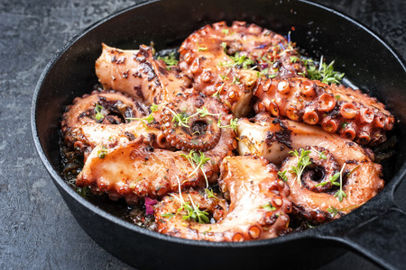 Traditional Spanish octopus braised cooked with tomatoes and herbs in wine sauce as closeup in a cast-iron saucepan Imagens