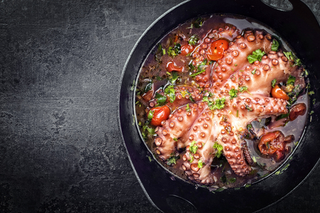 Traditional Greek octopus braised cooked with tomatoes and herbs in ouzo sauce as top view in a cast-iron saucepan with copy space left