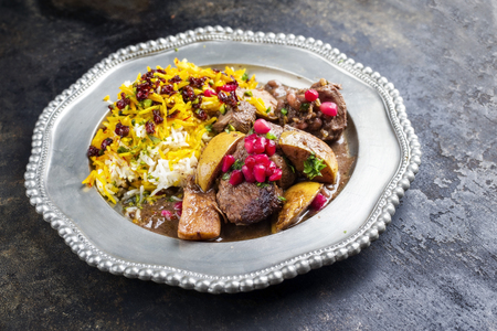 Traditional Iranian khoresh beh stew with chunks of lamb, quinces and saffron rice as a closeup on a pewter plate