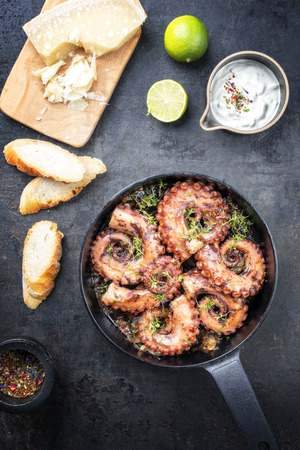 Traditional Spanish octopus braised cooked with aioli and baguette in wine sauce as top view in a cast-iron saucepan Stock Photo