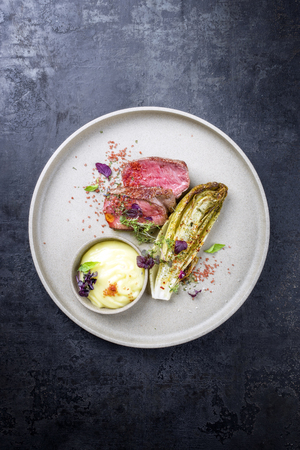 Barbecue wagyu point steak from beef sliced with chicory and mashed potatoes as top view on a modern design plate with copy space Imagens