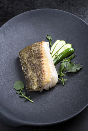 Fried Danish skrei cod fish filet with baby zucchini and lettuce as top view on a modern design plate Фото со стока