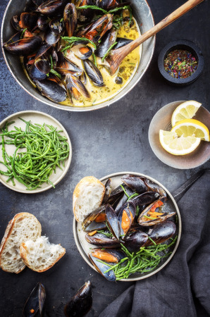 Traditional barbecue Italian blue mussel in white wine creme sauce with salicornia and baguette as top view in a casserole