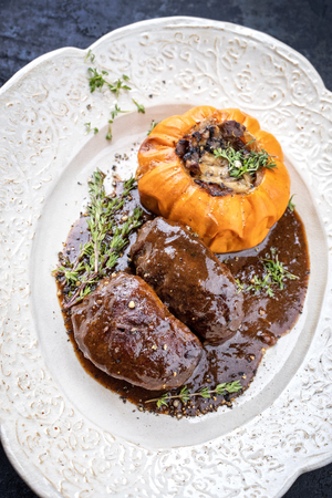 Traditional German braised pork cheeks in brown red wine sauce with mushroom and pumpkin as closeup on a shabby chic design white plate Stock Photo