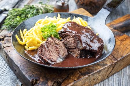 Carrilleras de ternera estofadas tradicional alemán en salsa de vino tinto marrón con hierbas spaetzle como primer plano en una sartén de hierro forjado sobre una tabla de madera