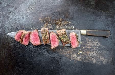 Traditioneel barbecue-gerijpt wildbraadstuk, gesneden met kruiden als bovenaanzicht op een groot mes met rustieke achtergrond met kopieerruimte