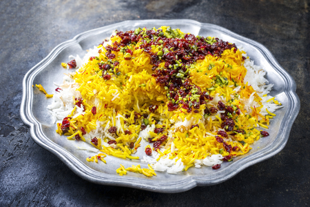 Traditional Iranian steamed saffron rice with berberis and pistachios as closeup on a pewter plate Banque d'images - 122125344