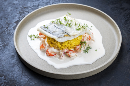Filet d'aiglefin frit avec riz au safran et crevettes à la sauce de crabe en gros plan sur une assiette au design moderne