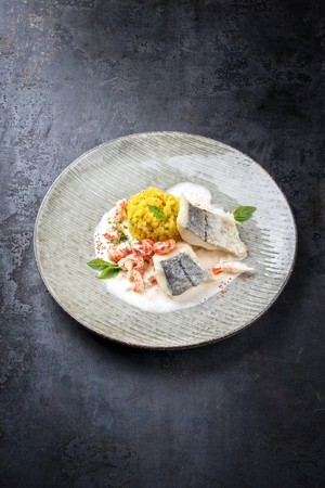 Fried haddock filet with saffron rice and shell prawns in crab sauce as top view on a modern design plate with copy space Banco de Imagens - 122125382