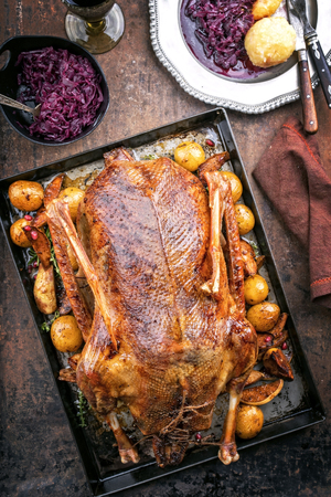 Traditional roasted stuffed Christmas goose with blue kraut, dumplings and potatoes as top view on a board Stock Photo