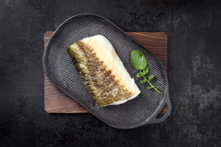 Fried Japanese skrei cod fish filet with wasabi lettuce as top view on a modern design plate  Stock fotó