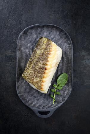 Filet de morue skrei japonais frit avec laitue wasabi en vue de dessus sur une assiette au design moderne