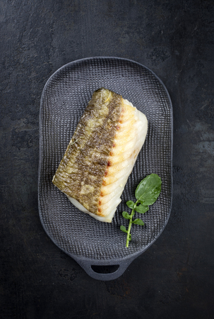 Fried Japanese skrei cod fish filet with wasabi lettuce as top view on a modern design plate  Фото со стока